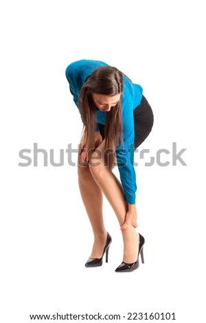 Business woman in high heels touching her ankle. Full body length isolated over white background.