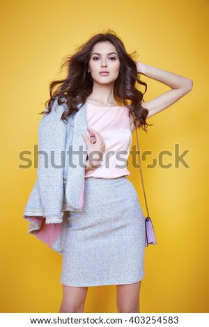 Business woman in office clothes wear costume flax jacket and skirt light blue silk pink hold hand lather bag goods accessory fashion style collection glamour pose model natural beauty makeup perfect
