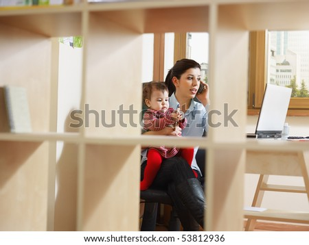business woman in office, holding her little girl while talking on mobile phone. Viewed through library. Horizontal shape, full length