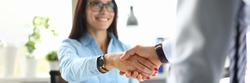 Business woman in office shakes hands with business partner. Mutually beneficial cooperation concept