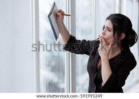 Business woman in office with a cigarette makes notes in notepad #591995249
