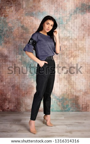 Business woman in pants and shirt on brick wall background. Office and business style. Studio photo.  #1316314316