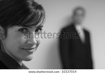 Business woman in purple looks towards camera with blurred man in black suit in background - stock photo