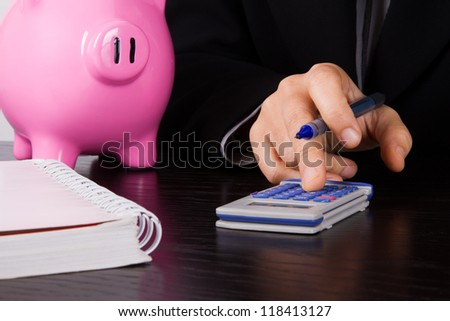 Business woman in suit calculating account on dark table.