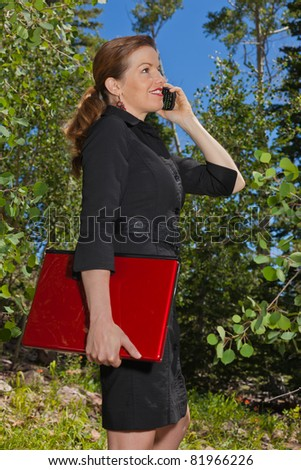 Business woman in the forest talking on her cell phone holding a laptop.