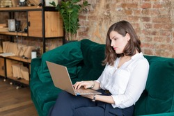 Business woman in white shirt working at laptop at home office. Hiring interviews.Distance learning.Sitting on dark green sofa. Brick wall.Remote work place.Quarantine of coronovirus pandemic covid-19