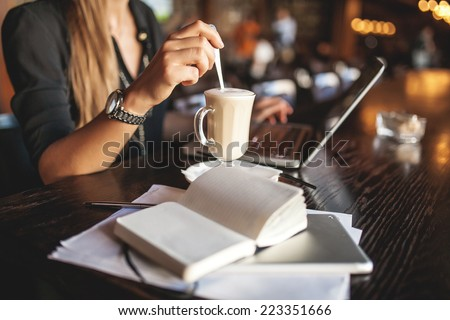Business woman indoor with coffee and laptop taking notes