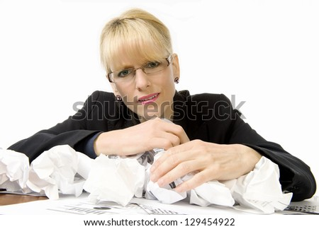 Business woman is dismayed as she works through pile of crumpled paper