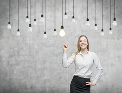 Business woman is pointing out the light bulbs. The concept of the innovative business strategy. Concrete background.