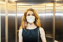 Business woman is using elevator during epidemic