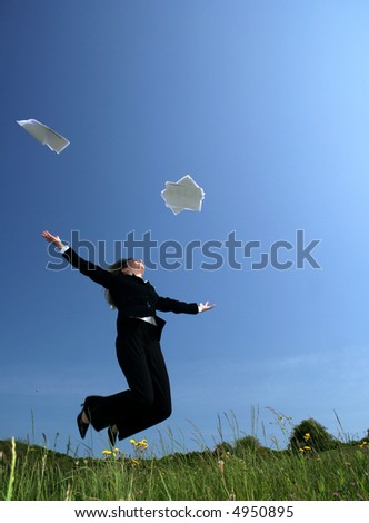 Business woman jumping and throwing papers into air.