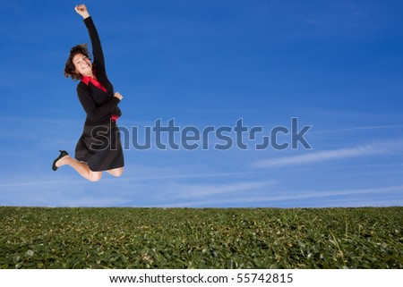 Business woman jumping high on a green hillside