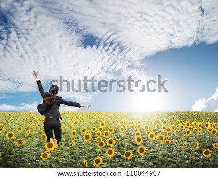 Business woman jumping in  blue sky over sunflowers field