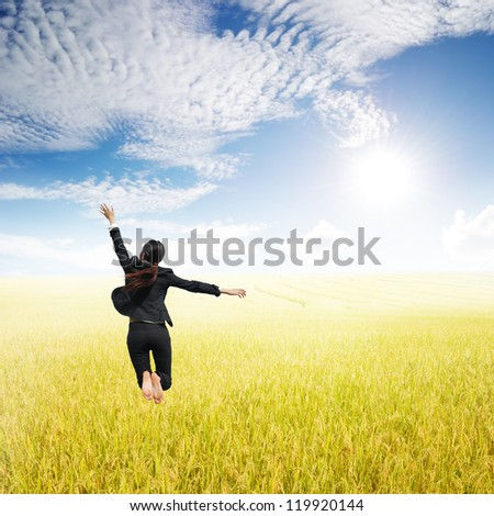 Business woman jumping in Yellow Rice fields and sun sky