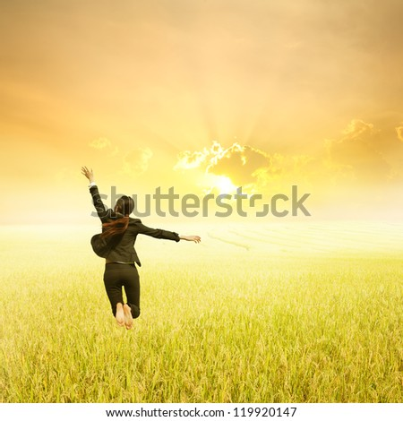 Business woman jumping in Yellow Rice fields and sunset