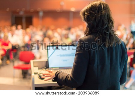 Business woman lecturing at Conference. Audience at the lecture hall.