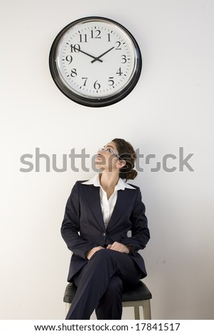 Business woman looking up at wall clock