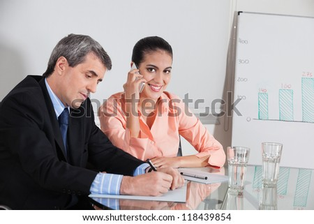 Business woman making a call in a meeting while a manager takes notes