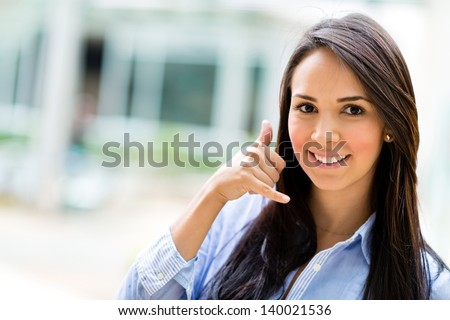 Business woman making a call me sign and smiling