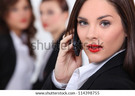 Business woman making call colleagues in background