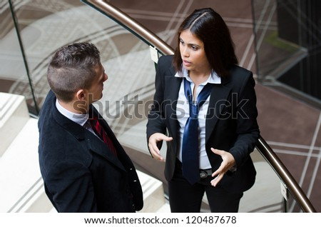Business woman making gestures while talking to a business man