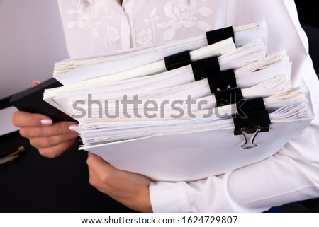 Business woman office workers holding are arranging documents of unfinished documents on office desk,Stack of business paper,document management,Businesswoman examining documents