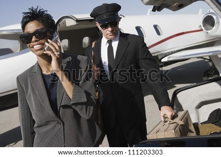 Business woman on a call while driver keeping luggage in car at airfield - stock photo