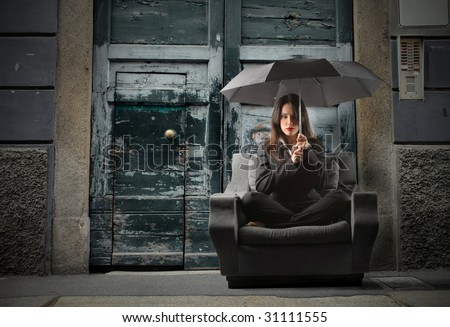 business woman on an armchair lost in countryside during a storm