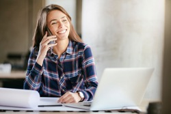 Business woman on the phone at office. Young business woman having phone call at the office. Smiling business woman. Pretty young business using smartphone at the loft office.