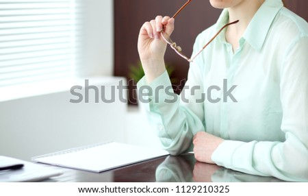 Business woman or secretary  sitting at the desk in the office. Green toned image #1129210325