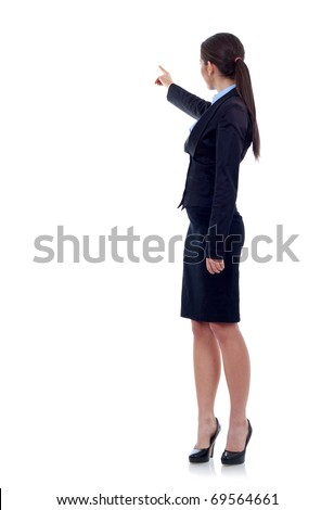 Business woman points finger at something in her back. Isolated on white background