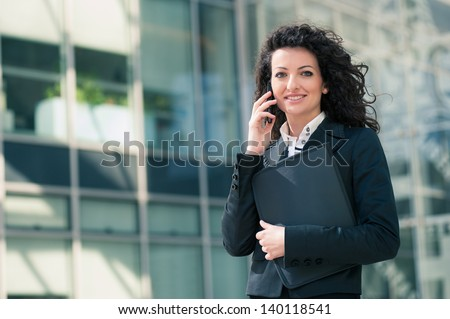 Business woman portrait outdoors talking at the phone with modern building as background. stock photo