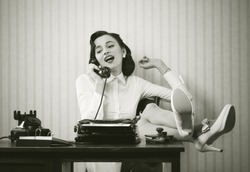 Business woman puts her feet up on her desk on the phone