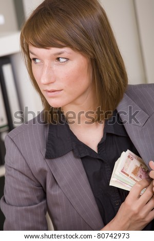 Business woman putting cash to her suit pocket - bribe scene