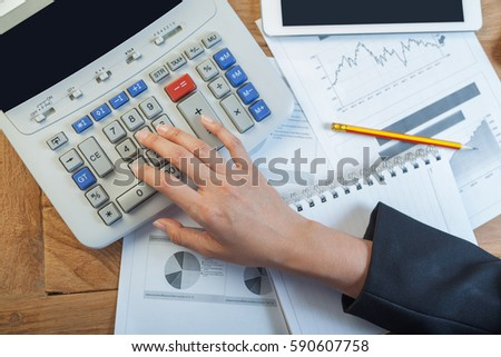 Business woman putting her hand on calculator, business and investment concept - Shutterstock ID 590607758