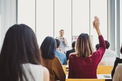 Business woman raising hand for asking speaker for question and answer concept in meeting room for seminar