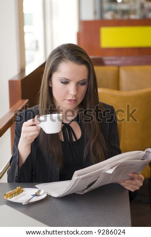 business woman relaxing in a bar drinking coffee and reading news paper