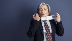 Business woman removes protective mask from her face. Focus on female face. Mature woman in formalwear on blue gray background. Copy space at left side. Close up portrait. Tinted image.