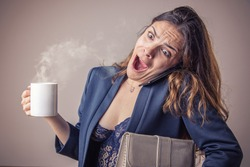 Business woman running late, holding her coffee, cell phone and files