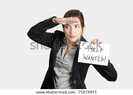 """Business woman search for help holding a cardboard with the text message """"Help Wanted"""""""