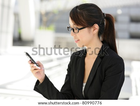 Business woman sending text message on mobile phone - stock photo