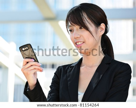 Business woman sending text message on mobile phone