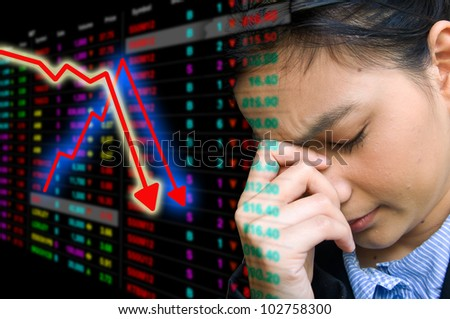 Business woman serious a falling down graph of stock market