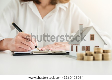 Business woman signing contract to buy house, insurance or loan real estate on table.