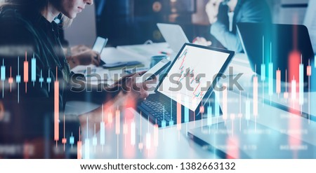 Business woman sitting front laptop computer with financial graphs and statistics on monitor. Double exposure. Wide