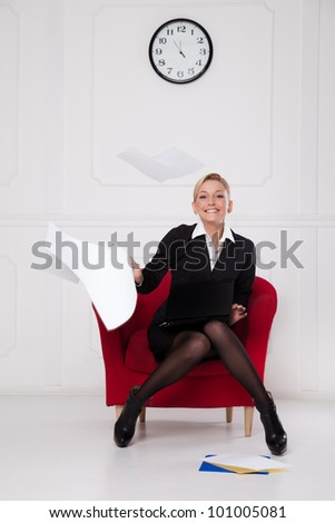 Business woman sitting in a chair and throws the paper into the air