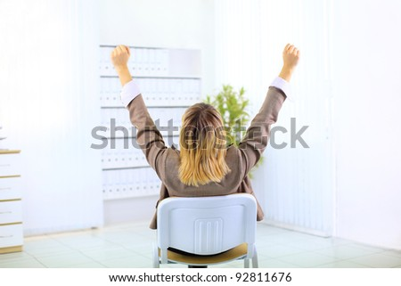 Business woman sitting in a chair and with her hands in the air celebrating success