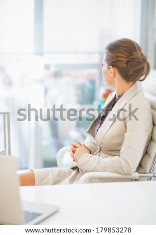 Business woman sitting in office and looking in window. rear view #179853278