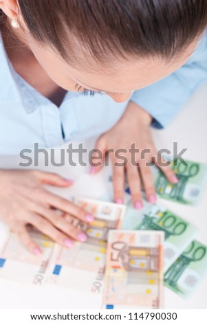 Business woman sitting with cash money, focus on her face