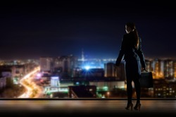Business woman standing at the window in the night office, through the window illuminated city